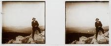 Homme assis sur un rocher face à un panorama montagnard