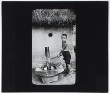 Enfant indigène annamite décortiquant du paddy